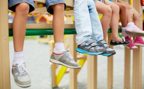 Kinderbeine mit unterschiedlichen Kinderschuhen an den Füßen
