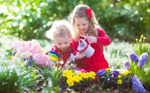 Kinder in Blumenbeet am Blumen gießen - Lieblingsplatz im Garten