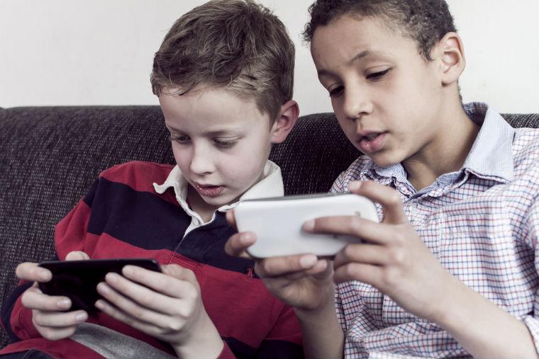 zwei Kinder schauen auf ein Smartphone