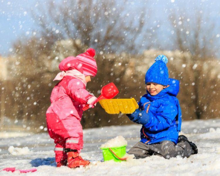 Kleinkinder spielen mit Spielzeug im Schnee