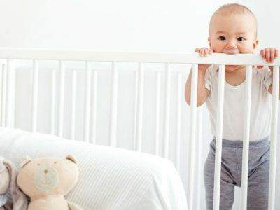 Baby steht in einem Babybett