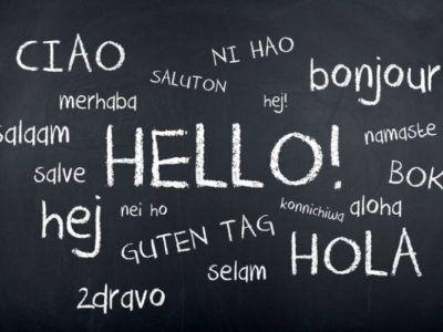 """""""Hallo"""" in verschiedenen Sprachen mit weißer Kreise auf schwarzer Tafel zur Andeutung der zweisprachigen Erziehung"""