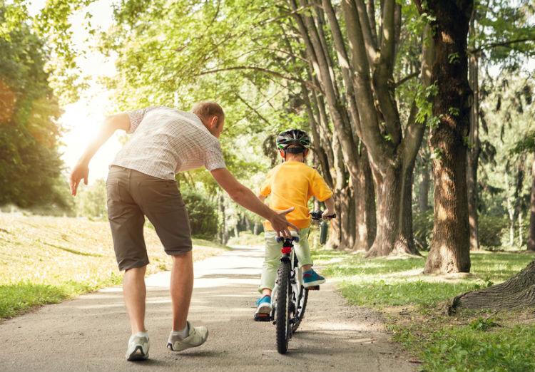 Kinde lernt Fahrradfahren mit Vater
