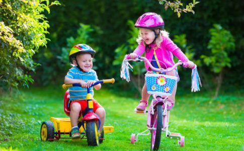 Kinderfahrzeug - Jnge auf Dreirad und Mädchen auf Fahrrad im Garten