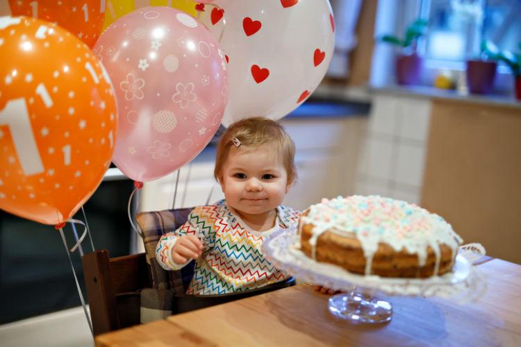 Kleines Mädchen mit Geburtstagskuchen und Ballons, auf denen eine 1 steht