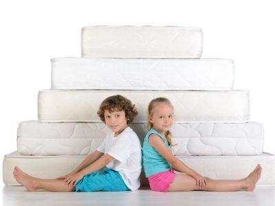 Zwei Kinder die vor Matratzen sitzen