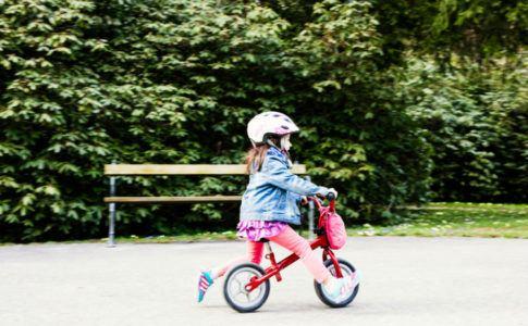 Kleines Mädchen mit Helm, das auf einem Laufrad Fahrradfahren lernt