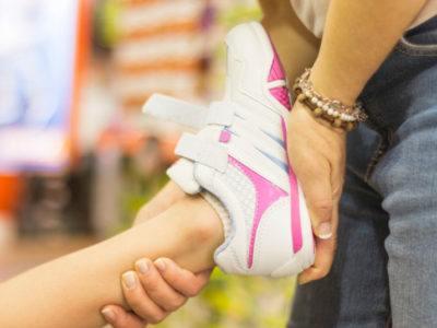 Kinderschuhe kaufen - Mutter zieht Kind Schuh an