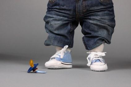 Ein Kind mit hellblauen Kinderschuhen und einem blauen Schnuller auf dem Boden