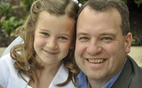 Vater mit Tochter bei der Kommunion