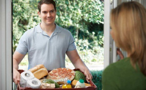 Lieferant liefert eine Lebensmittelbestellung direkt zur Haustür, an der eine Frau die Lieferung entgegen nimmt.
