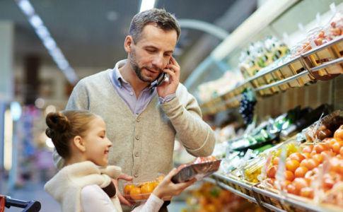 Vater und Tochter kaufen Lebensmittel und prüfen dabei Gütesiegel