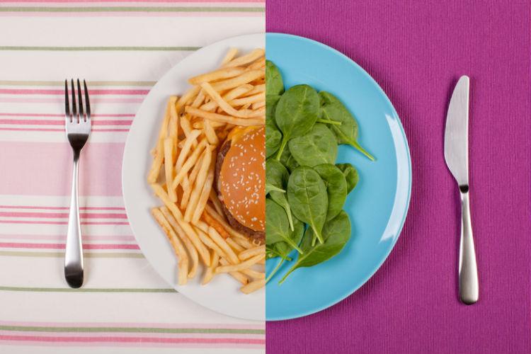 Ein Teller, auf dem auf der einen Seite Fast Food und auf der anderen Seite Salat zu sehen ist