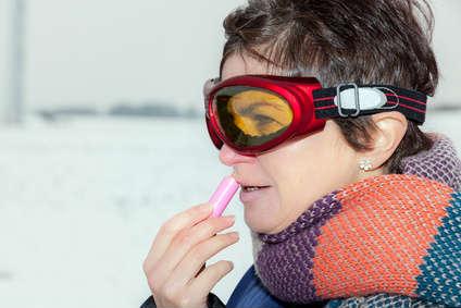 Eine Frau mit Schal und Skibrille benutzt einen Labello.