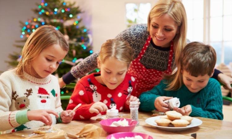 Drei Kinder backen mit ihrer Mutter Kekse