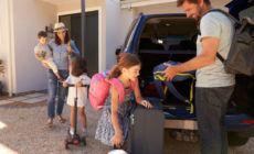 Familie packt ihre Koffer in ein Auto, um in den Urlaub zu fahren