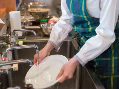 Person die als Tellerwäscher in den Ferien arbeitet
