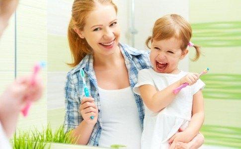 Glückliche Mutter putzt mit ihrem glücklichen Kind die Zähne mit Zahnbürsten