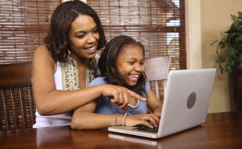 Mutter sitzt mit der Tochter am Laptop