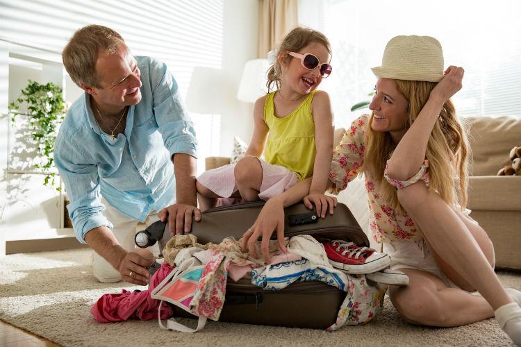 Dreiköpfige Familie versucht übervollen Koffer für Familienurlaub zu schließen