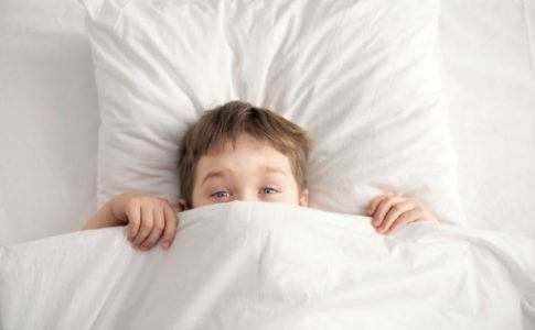 Ein Junge versteckt sich unter der Bettdecke