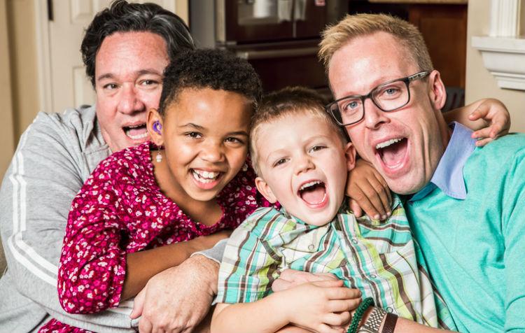 Homosexuelles Paar auf lustigem Familienfoto mit ihren zwei Pflegesöhnen
