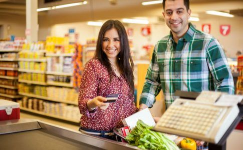Junges Paar bezahlt Einkauf vom Gemeinschaftskonto