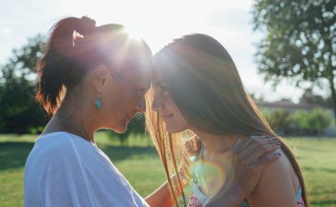 Mutter und Tochter Stirn an Stirn im Sonnenschein