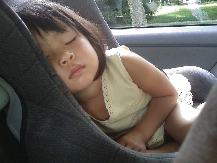 Mädchen schläft im Kindersitz auf dem Rücksitz eines Autos