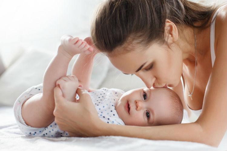 Mutter gibt ihrem lachendem Baby im Strampler einen Kuss auf den Kopf