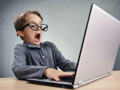 Schockiert und überrascht Junge im Internet am Laptop