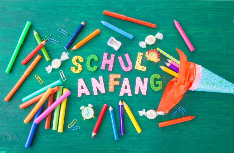 Stifte, Bonbons und eine kleine Schultüte auf einer Tafel