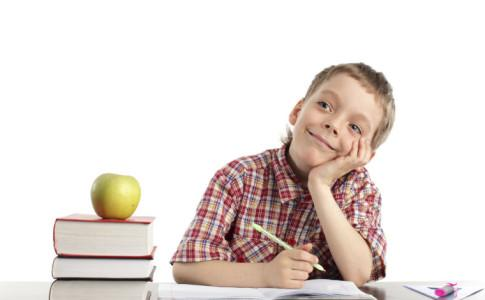 Schulkind mit Büchern und Apfel neben sich