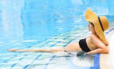 Schwangere Frau liegt im Pool