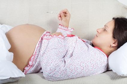 Schwangere Frau liegt auf dem Sofa und hat ein Fiberthermometer in der Hand.