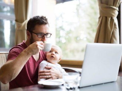 Selbstständiger Mann sitzt mit Baby vor dem Laptop und arbeitet