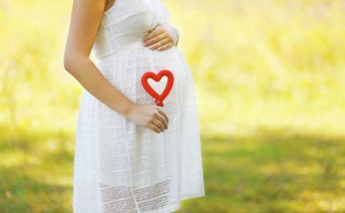 Schwangere Frau in einem weißen Kleid im Sommer