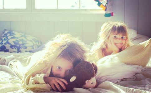 Zwei Mädchen im Kinderzimmer, in dem viel Sonne ist