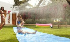 Familie hat Spaß bei Spielen mit Wasser im Garten