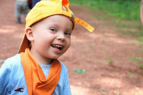 Kind lachend mit gelber Mütze