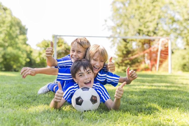 Drei Jungs liegen draußen mit einem Fußball auf der Wiese und lachen