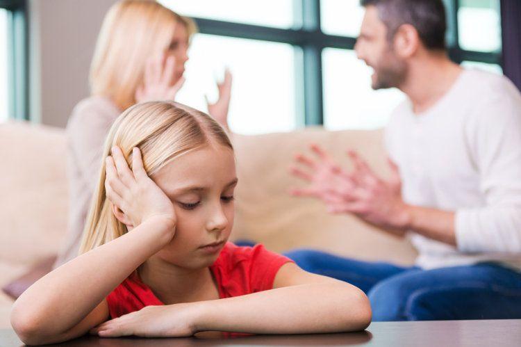 Betrübtes Kind im Fokus mit streitenden Eltern im Hintergrund