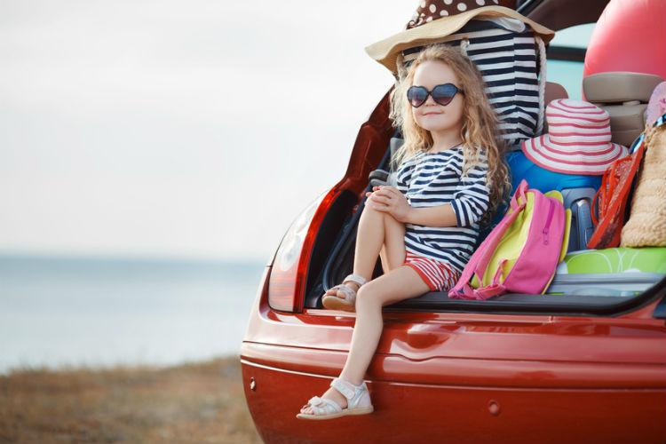 junges Mädchen sitzt in Kofferraum zwischen Gepäck