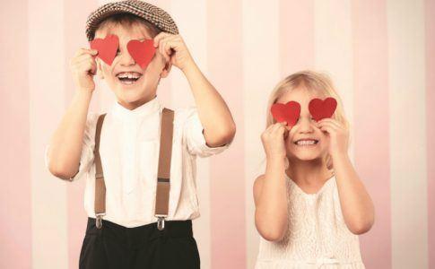 Einen schönen Valentinstag mit der Familie - zwei Kinder halten sich rote Papierherzen vor die Augen