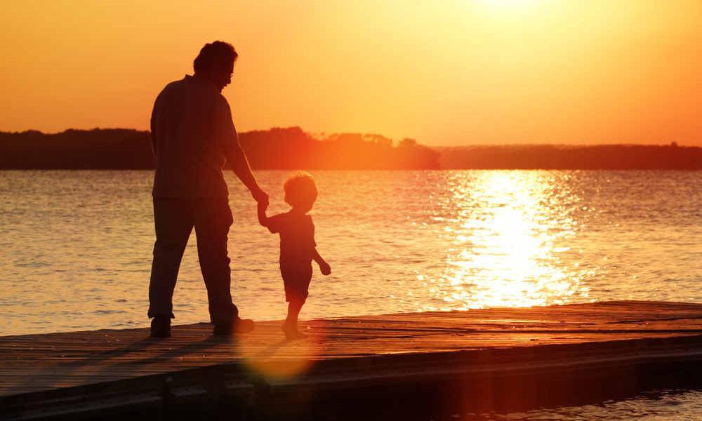 Vater spaziert mit seinem Sohn am Strand
