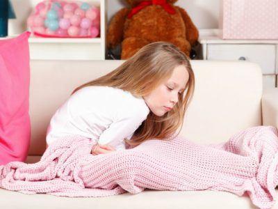 Mädchen sitzt auf Bett und hält sich den Bauch vor Schmerzen
