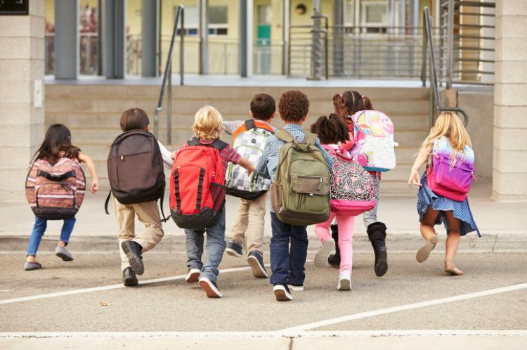 Kinder, die mit Schulranzen zur Schule laufen