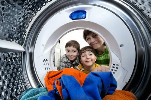 Kinder schauen in eine Waschmaschine.