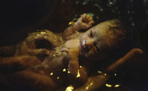 Neugeborenes wird im Wasser von Mutter gehalten