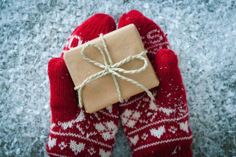 weihnachtliche Handschuhe halten Geschenk